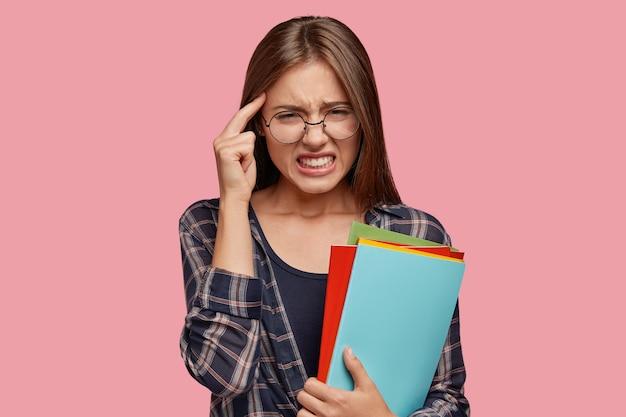 Foto interna de uma mulher europeia estressante com a mão na têmpora, dor de cabeça, cerrando os dentes Foto gratuita