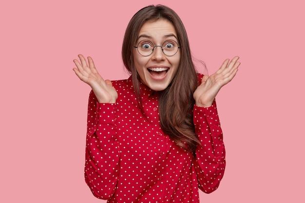 Foto interna de uma mulher morena positiva com uma camisa de bolinhas vermelhas, mantém as mãos perto do rosto, sente-se feliz, tem uma expressão facial radiante, modelos sobre um fundo rosa Foto gratuita