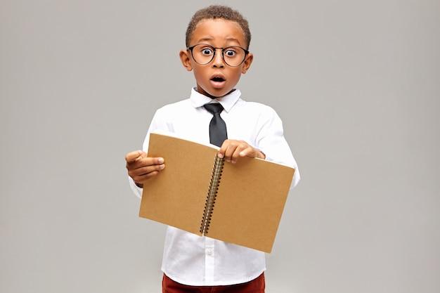 Foto isolada de um aluno africano chocado emocionalmente, vestindo camisa branca, gravata preta e óculos com olhar surpreso e surpreso, mantendo a boca aberta, segurando um caderno em branco aberto nas mãos Foto gratuita