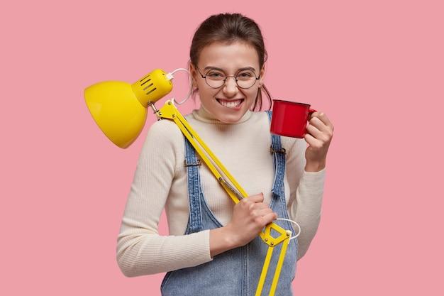 Foto isolada de uma mulher sorridente atraente morde o lábio inferior, usa óculos redondos, macacão jeans, se diverte durante a pausa para o café e carrega um lampião Foto gratuita