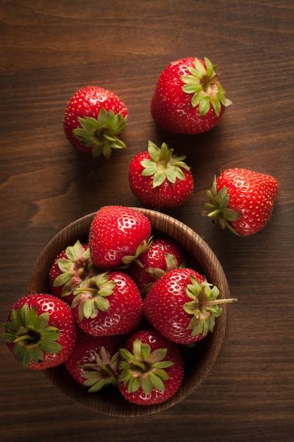 Foto macro de morango vermelho maduro fresco em uma tigela de madeira com fundo rústico. produtos naturais orgânicos. Foto Premium