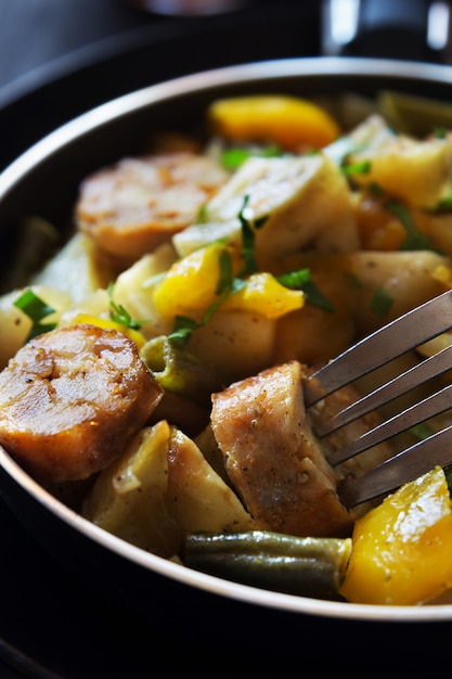 Foto macro vertical de batatas fritas com salsichas, feijão e pimenta Foto Premium