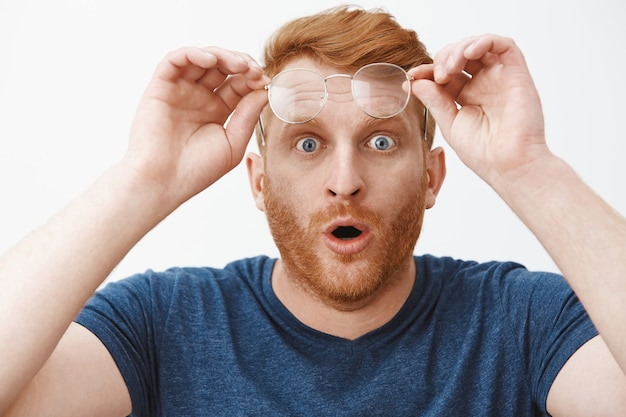 Foto na cabeça de um ruivo surpreso e impressionado com barba, tirando os óculos e segurando o aro na testa, dobrando os lábios e olhando com olhos arregalados para algo impressionante e curioso Foto gratuita