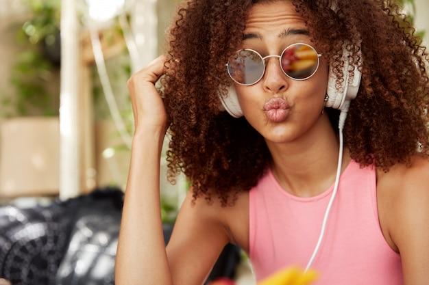 Foto na cabeça de uma mulher elegante e agradável em tons com penteado africano, lábios arredondados, expressão engraçada, música ou áudio favoritos em fones de ouvido no site de rádio. conceito de pessoas e estilo Foto gratuita