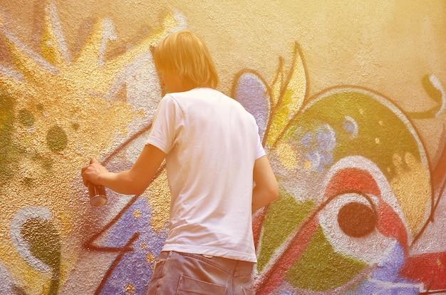 Foto no processo de desenhar um padrão de grafite em um velho muro de concreto Foto Premium