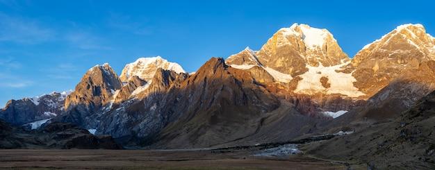 Foto panorâmica de um vale na cordilheira base huyahuash, peru, com seu pico coberto de neve. Foto gratuita