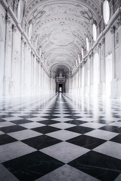 Foto preto e branco de um belo edifício com esculturas e um piso de xadrez Foto gratuita