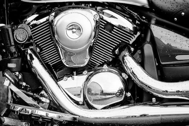 Foto preto e branco do close up do motor da motocicleta com muitos detalhes do cromo. motocicleta de estrada poderoso desempenho moderno com tubos de escape. motor chopper. Foto Premium