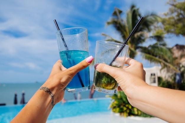 Foto próxima de mãos segurando coquetéis de álcool Foto gratuita