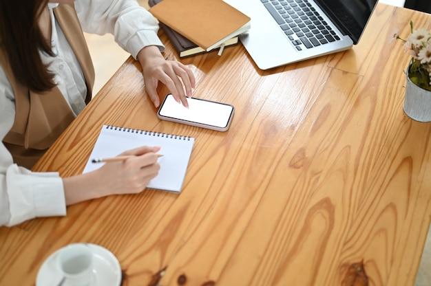 Foto recortada da mulher de desingner escrevendo seu projeto no notebook enquanto usa o smartphone com tela branca Foto Premium