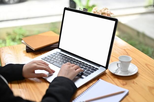 Foto recortada de bussinesswoman usando laptop com tela branca na mesa de madeira. Foto Premium