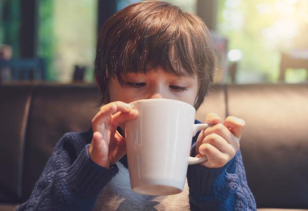 Foto recortada de criança bebendo chocolate quente no café com um tom quente, menino saudável criança soprando bebida quente na cafeteria no inverno. Foto Premium
