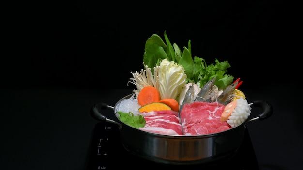Foto recortada de delicioso shabu shabu em uma panela quente com fundo preto Foto Premium