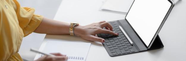 Foto recortada de empreendedor feminino, concentrando-se em seu trabalho com tablet digital Foto Premium