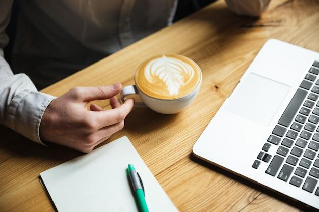 Foto recortada de mans mão na camisa branca, segurando a xícara de café Foto gratuita