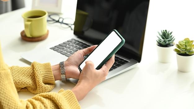 Foto recortada de mãos de mulher jovem ocupadas usando telefone celular com tela vazia na mesa de trabalho. Foto Premium