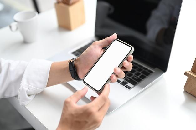 Foto recortada de mãos segurando um telefone inteligente com tela vazia na mesa de escritório branca. Foto Premium