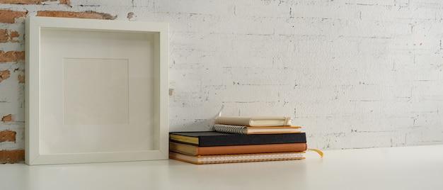 Foto recortada de mesa de trabalho com moldura simulada, livros, cadernos e espaço de cópia na mesa do escritório doméstico Foto Premium