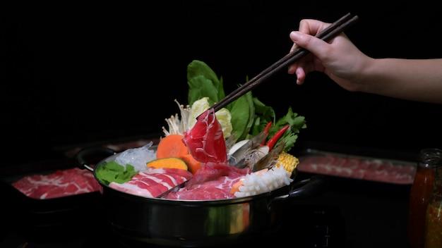Foto recortada de mulher comendo shabu-shabu em panela quente com carne fresca fatiada, frutos do mar e legumes com fundo preto Foto Premium