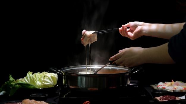 Foto recortada de mulher comendo shabu-shabu em panela quente com carne fresca fatiada, mergulhando em queijo com fundo preto Foto Premium