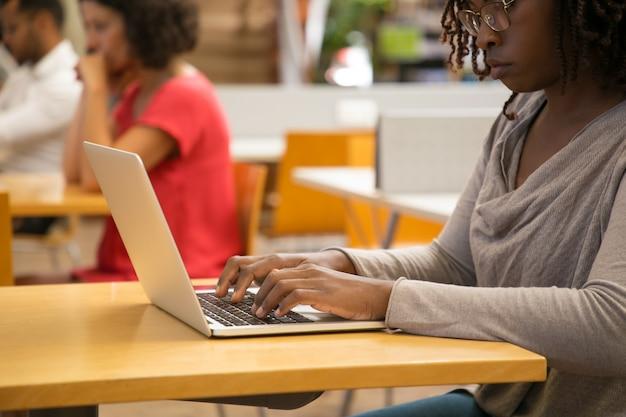 Foto recortada de mulher pensativa, trabalhando com o laptop na biblioteca Foto gratuita