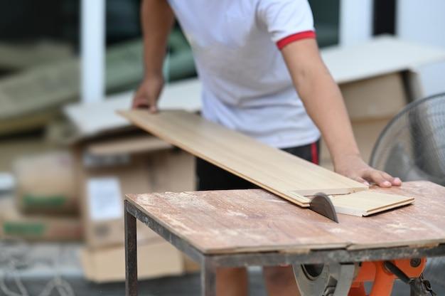 Foto recortada de um carpinteiro cortando um pedaço de madeira em sua oficina de marcenaria. Foto Premium