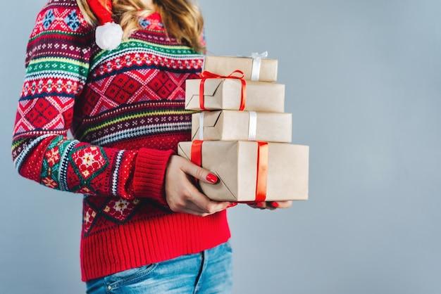 Foto recortada de uma menina loira com unhas vermelhas esmaltadas segurando um monte de caixas de presente embrulhadas em papel artesanal e decoradas com fita de cetim vermelha Foto Premium