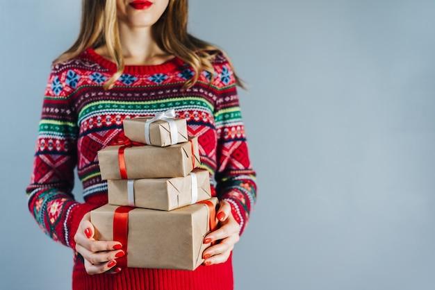 Foto recortada de uma menina loira sorridente com lábios vermelhos e unhas polidas segurando um monte de caixas de presente embrulhadas em papel artesanal e decoradas com fita de cetim vermelha Foto Premium