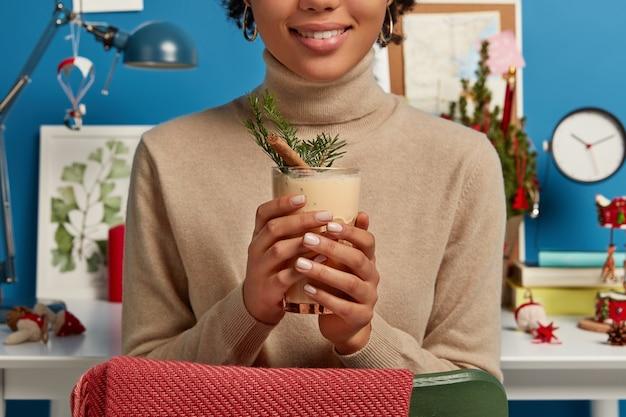 Foto recortada de uma mulher com um suéter marrom segurando uma saborosa bebida tradicional de natal cheia de canela e abeto Foto gratuita