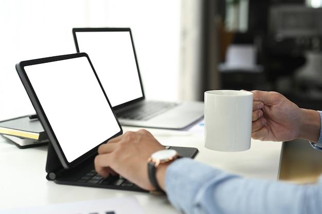 Foto recortada do empresário trabalhando no tablet do computador enquanto a mão segurando a xícara de café no escritório. Foto Premium