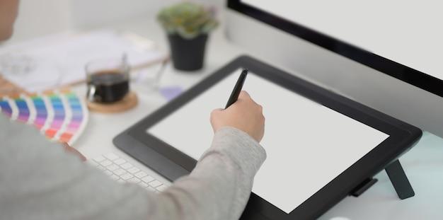 Foto recortada do jovem designer profissional feminino, editando seu projeto com tablet digital Foto Premium