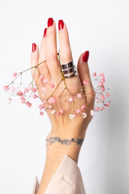 Foto suave suave da mão de uma mulher com manicure de anel grande vermelho segurar lindas flores secas rosa em branco. Foto gratuita