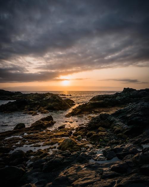 Foto vertical de alto ângulo das formações rochosas na costa do mar sob o céu nublado Foto gratuita