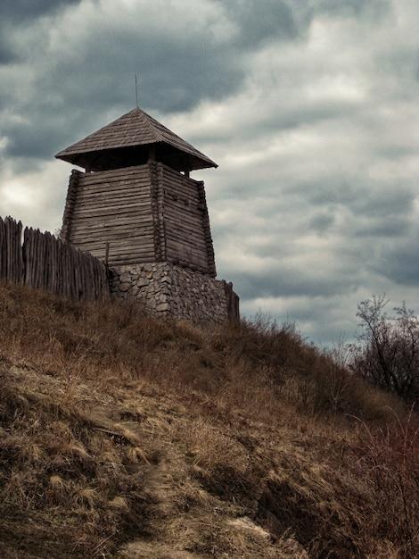 Foto vertical de baixo ângulo de uma construção de madeira perto de uma cerca sob um céu nublado Foto gratuita
