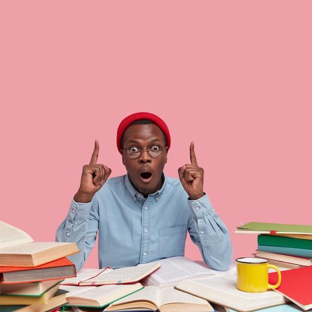 Foto vertical de homem negro surpreso com expressão de espanto, apontando para o teto com os dois dedos indicadores, vestindo roupas da moda Foto gratuita