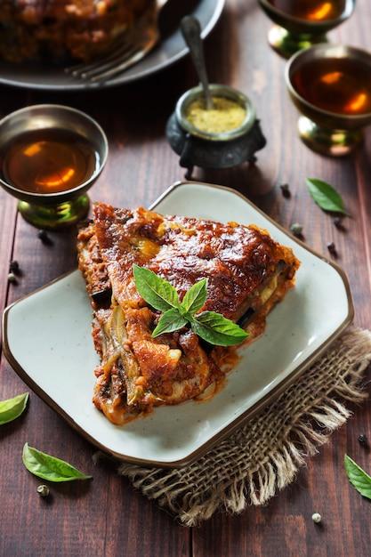 Foto vertical de lasanha de berinjela com queijo, carne, molho de tomate e manjericão Foto Premium