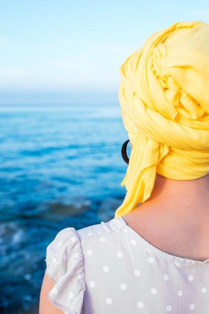 Foto vertical de mulher com um lenço amarelo, apreciando a vista do mar Foto gratuita