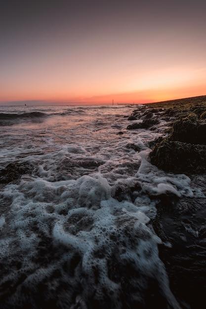 Foto vertical de ondas espumosas do mar chegando à costa com o incrível pôr do sol Foto gratuita