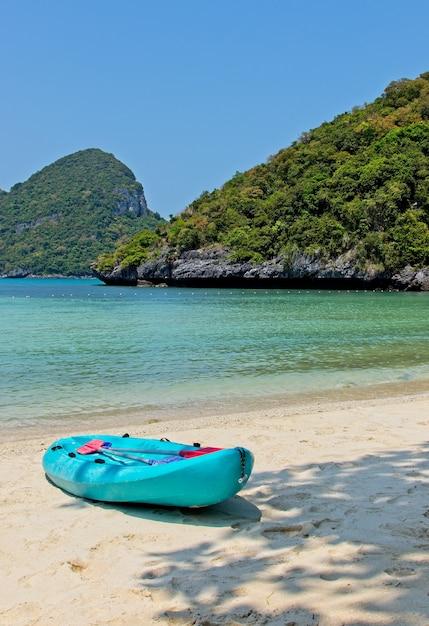 Foto vertical de um barco a remo azul na praia, perto do belo oceano e das montanhas Foto gratuita