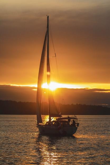 Foto vertical de um barco à vela no oceano durante o pôr do sol Foto gratuita