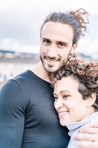 Foto vertical de um casal abraçado pelo ombro com o mar fora de foco Foto gratuita