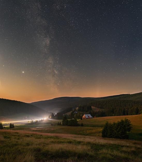 Foto vertical de um céu noturno estrelado com a via láctea sobre as montanhas gigantes Foto gratuita