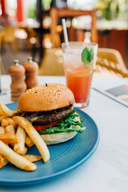 Foto vertical de um hambúrguer delicioso e algumas batatas fritas e um copo de coquetel na mesa Foto gratuita