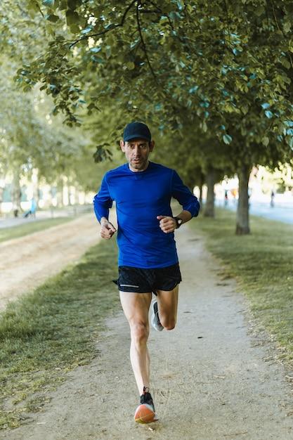 Foto vertical de um homem correndo na rua - um estilo de vida saudável Foto gratuita