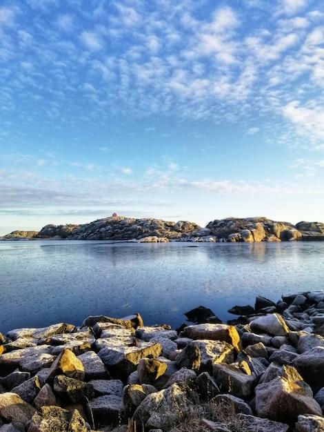 Foto vertical de um lago cercado por formações rochosas em stavern, noruega Foto gratuita