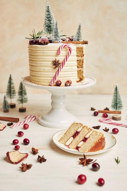 Foto vertical de um pedaço de bolo em um prato e um bolo de natal Foto gratuita