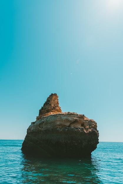 Foto vertical de um penhasco rochoso no mar sob o céu claro Foto gratuita