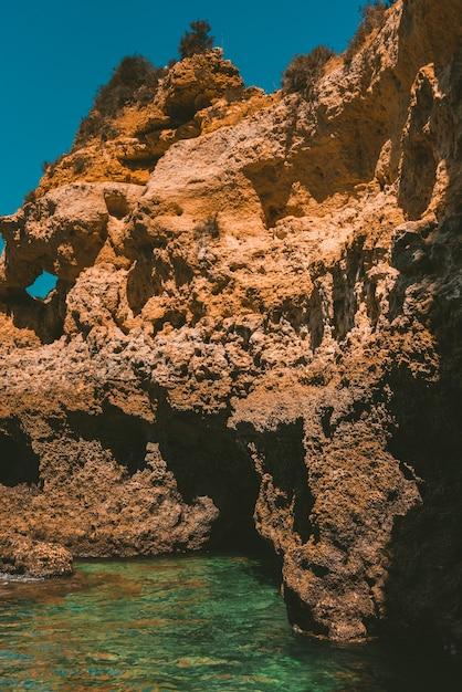 Foto vertical de um penhasco rochoso refletindo no mar em um dia ensolarado Foto gratuita