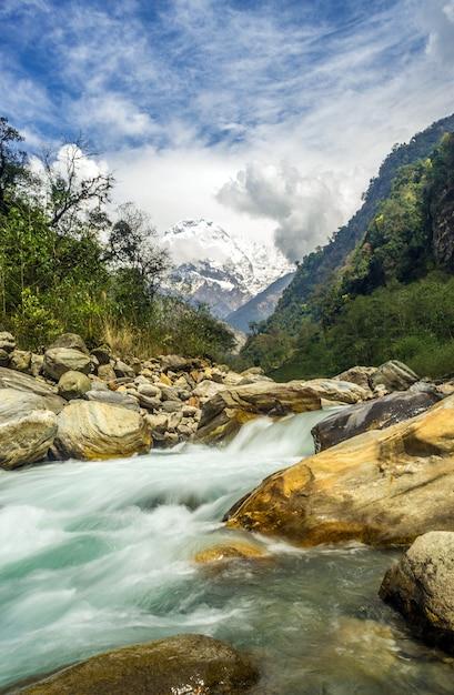 Foto vertical de um rio rápido batendo nas rochas com montanhas Foto gratuita