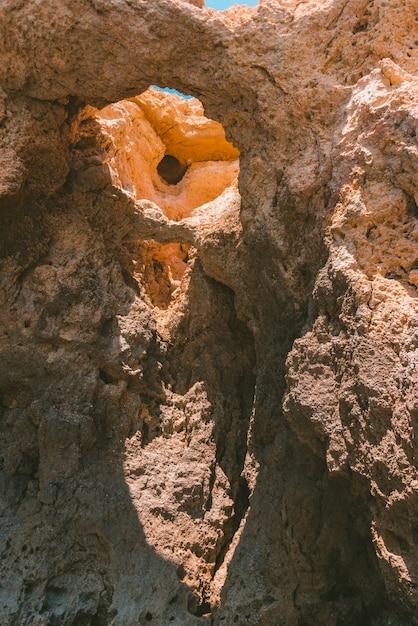 Foto vertical de uma antiga formação rochosa com buracos Foto gratuita